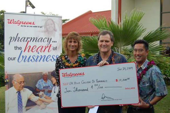 Dr. John M. Pezzuto, dean of the UH-Hilo College of Pharmacy, accepts a $10,000 donation from Dana Psomas, left, Walgreens' Hawaii district manager, and Clark Fujihara, Walgreens district pharmacy supervisor, on Tuesday, Jan. 20, during a gathering of first-year pharmacy students on the campus. (Photo courtesy of Marc Burba)