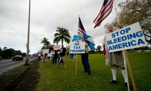 Over a hundred people wave signs and flags in Hilo for the Tax Day Tea Party demonstration. Photography by Baron Sekiya/Hawaii247.com