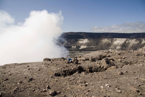 A lone blue plastic bucket sampler braves the crater's edge near the Overlook vent with HVO on the horizon. (Photo courtesy of Hawaiian Volcano Observatory)