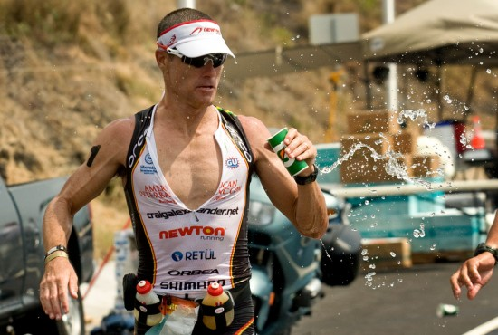 Craig Alexander goes for hydration on the marathon course of the Ironman Triathlon. Heat and humidity are taking their toll on runners. Photography by Baron Sekiya for Hawaii 24/7.