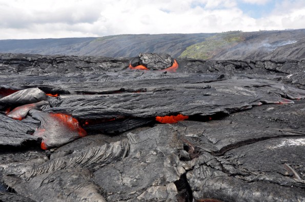The western branch of the coastal plain flow field is inflated and more active than the eastern branch. Here, a breakout from a tumuli feeds a ropey pahoehoe flow. The fume in the background on the pali marks the lava flow activity that is feeding the coastal breakouts. Photo courtesy of USGS/HVO