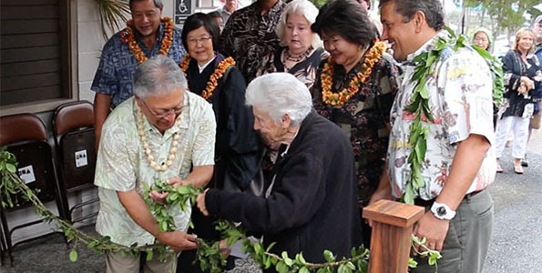 Glenn Yano and former State Rep. Virginia Isbell untie the maile lei Tuesday to reopen Yano Hall. Looking on is Managing Director Wally Lau, Reverend Jiko Nakade, Councilmembers Dru Mamo Kanuha and Brenda Ford, Kona Regional Senior Club President Sharen Bangay, and Mayor Billy Kenoi. (Photo courtesy of the Mayor's Office)