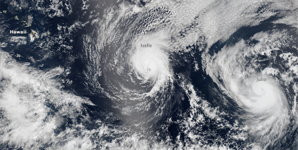 """On August 5 2014, the Visible Infrared Imaging Radiometer Suite (VIIRS) sensor on Suomi-NPP captured natural-color images of both Iselle and Hurricane Julio en route to Hawaii. The image above is a composite of three satellite passes over the tropical Pacific Ocean in the early afternoon. Note that Iselle's eyewall had grown less distinct; the storm had descreased to category 2 intensity. The bright shading toward the center-left of the image is sunglint, the reflection of sunlight off the water and directly back at the satellite sensor. NASA image by Jeff Schmaltz, LANCE/EOSDIS Rapid Response."""" width=""""595"""" height=""""396"""" /> On August 5 2014, the Visible Infrared Imaging Radiometer Suite (VIIRS) sensor on Suomi-NPP captured natural-color images of both Iselle and Hurricane Julio en route to Hawaii. The image above is a composite of three satellite passes over the tropical Pacific Ocean in the early afternoon. Note that Iselle's eyewall had grown less distinct; the storm had descreased to category 2 intensity. The bright shading toward the center-left of the image is sunglint, the reflection of sunlight off the water and directly back at the satellite sensor. NASA image by Jeff Schmaltz, LANCE/EOSDIS Rapid Response."""