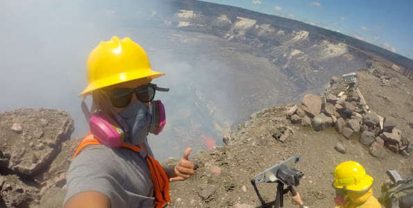 """Greg Javar snaps a """"selfie"""" while helping USGS Hawaiian Volcano Observatory geologist Matt Patrick (right) set up a thermal camera to record lava lake activity within the summit vent of Kīlauea Volcano. Javar and fellow UH-Mānoa student Pua Pali (not shown) were selected to intern at HVO this summer through the Native Hawaiian Science and Engineering Mentorship Program."""