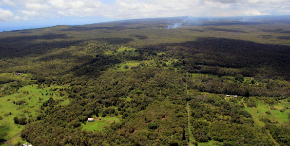 This wide view taken Monday (Sept 1), looking west, shows the position of the June 27th flow front relative to the nearby Kaohe Homesteads subdivision. The front of the flow is moving through thick forest, and its position can be seen by the plumes of smoke above the center of the photograph. Near these active surface flows, there was also steaming from a ground crack, resulting from lava deep in the crack. The farthest point of this steaming was 1.7 km (1.1 miles) west of the boundary of the Kaohe Homesteads subdivision. Photo courtesy of USGS/HVO