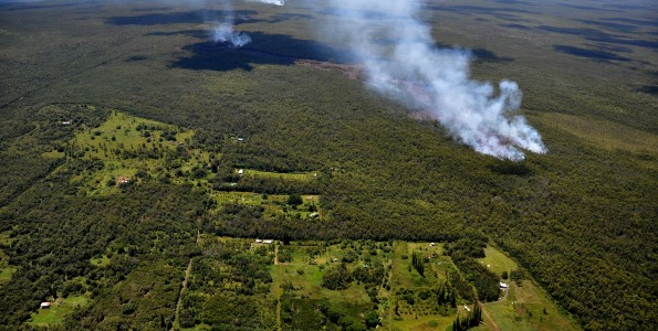 As of Friday afternoon, September 12, 2014, the most distal front of the June 27th lava flow had reached a straight-line distance of 14.9 km (9.3 miles) from the source vent on the northeast flank of the Puʻu ʻŌʻō cone. The flow has continued in the northeast direction that it assumed in the middle of the week and is now only 171 meters (0.1 miles) from the boundary of the Kaohe Homesteads community. The flow is still within thick forest, so that dense plumes of smoke are created as vegetation is consumed. Small breakouts (visible as plumes in the middle distance) are also active closer to Puʻu ʻŌʻō, roughly midway along the length of the June 27th flow. Photo courtesy of USGS/HVO