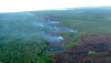 The leading edge of the Kilauea June 27th lava flow on the left with outbreaks upslope on its North side, where the smoke is, along with the dark burn scar from the brushfire covering much of the bottom right of the photo. Photo taken Friday morning, September 26, 2014. Photograph courtesy of Hawaii County.