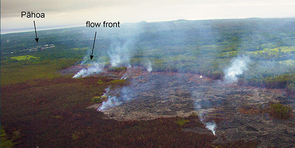 Another view of the flow front on October 17, 2014, looking downslope towards Pāhoa. The smoke plumes are created by individual breakouts burning vegetation at the flow margin. Photo courtesy of USGS/HVO