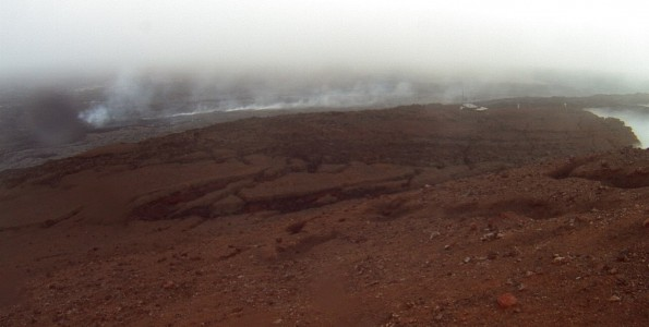 A photo looking west from a research camera temporarily positioned southeast of the Pāhoa Marketplace, this image shows the June 27th lava flow advancing from left to right. The image was taken at 6:55 a.m. Monday, March 2, 2015. This camera that took this was installed through a collaboration between the USGS Hawaiian Volcano Observatory, Oceanic Time Warner Cable, and Bryson's Cinders Inc.