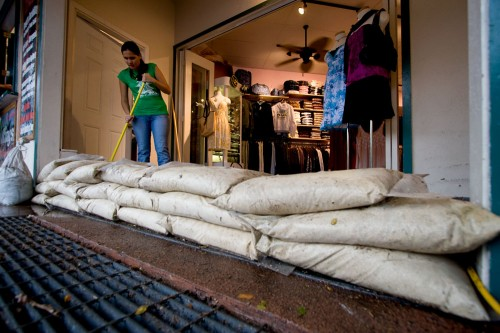Tiere Ubando sweeps debris from Honolua Wahine, at the Kona Inn Shopping Center on Alii Drive, after rainstorms and street flooding occurred Thursday afternoon. Shopping center crews sandbagged the entrance to prevent flooding into the shop.