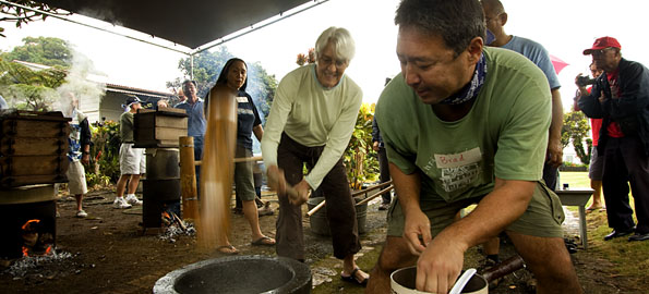 Sue Irvine, of Hilo, left, swings a mallet to pound sweet steamed rice into mochi as Brad Kurokawa wets his hands between turning the hot rice dough. Kurokawa has to be quick and in sync with Irvine so his hand isn't turning the dough when the mallet hits it. (Photos and video by Baron Sekiya/Hawaii247.com)