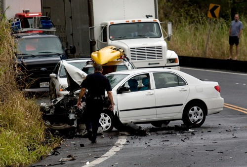 An officer checks on one of the three vehicles involved in an accident at Kaawalii Gulch.