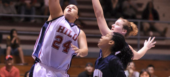Hilo's Sheila Azevedo lays up the ball beyond the reach of NDNU's #23 Jennifer Dreessen and #32 Tanaia Keyes.