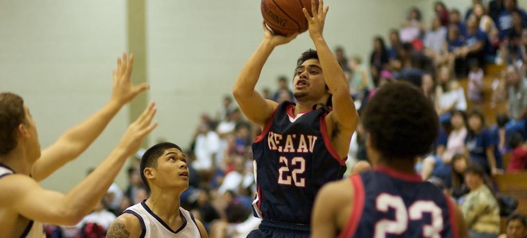 Keaau's Makana Cazimero (22) takes a jumper as Waiakea's Matthew Libao (15) and fellow Cougar Jelani Young (23) watch during BIIF basketball action at Waiakea. Waiakea wins in overtime 59-55.