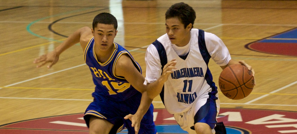 Hilo's Dylan Guthier (15) guards Kamehameha-Hawaii's Kawika Cazimero (11) during the third-place game for the BIIF Div-I at Afook-Chinen Civic Auditorium. Kamehameha-Hawaii wins 70-64.