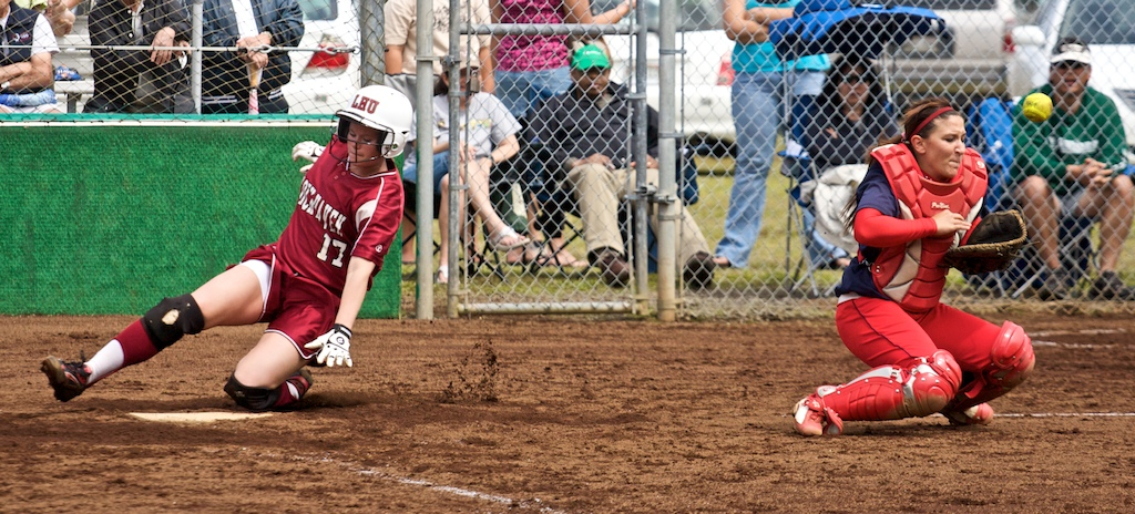 Lock Haven's Nancy O'Connor scores as UH-Hilo catcher Jessica Schatz can't make the play at home during the first game of a doubleheader in Hilo. Lock Haven took the first game 2-1 and lost the second to the Vulcans 1-0. Photos by Baron Sekiya/Hawaii247.com