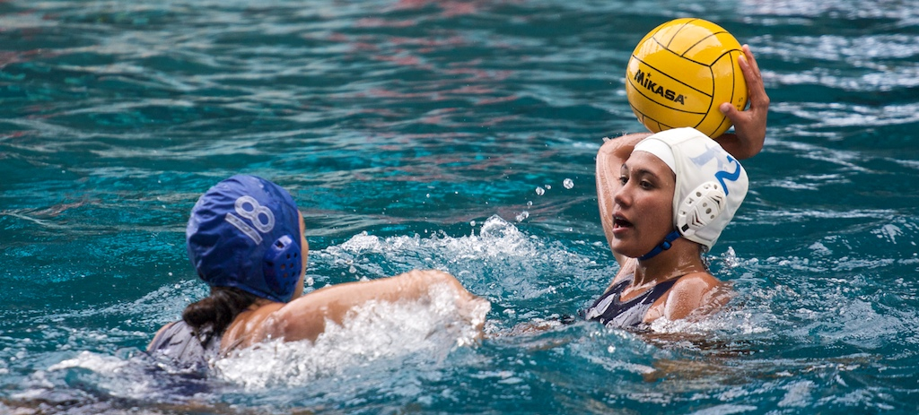 Kealakehe's Kylan Mullineaux (2) lines up a shot with Waiakea's Kandrie Herring (18) defending during BIIF water polo action at Kawamoto Pool.