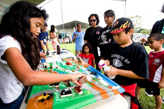 Ericka Paiva, left, sprinkles some dye onto a miniature cityscape as Kinyaaaanii Padilla, right, provides the simulated rainstorm in a demonstration of water runoff at the Department of Health Clean Water Branch booth.