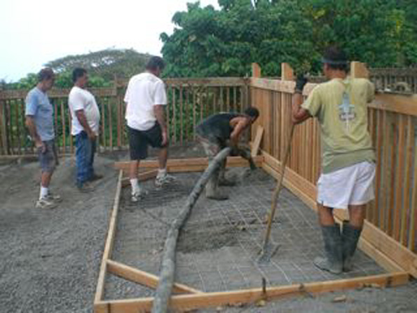 Pouring the concrete for the 1-year-old play area. Lucky keiki thanks to Lucky's Pumping.