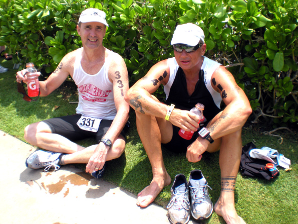 Adam Busek, 47, of Keaau, and Bill Greineisen, 56, of Volcano, relax and enjoy some post-race refreshments. (Hawaii247.com photo by Karin Stanton)