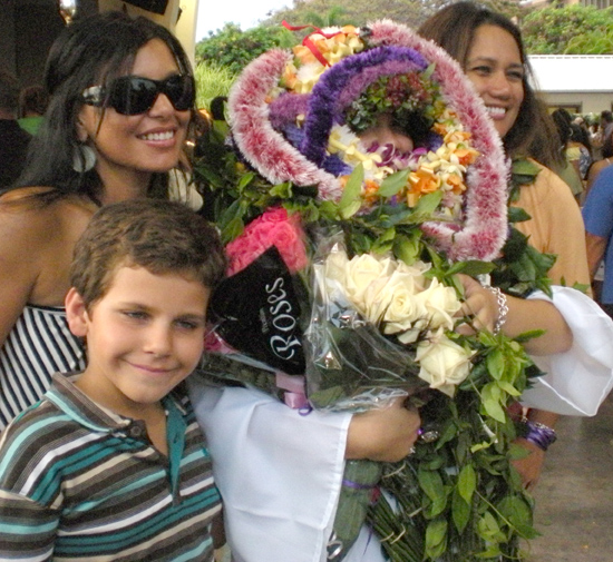 Buried in leis and flowers, Makua Lani Christian Academy senior Alexa Rae Kam poses for some family snaps.