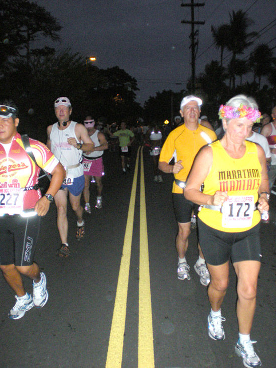 Marathon runners take off along Alii Drive at the start of the Kona Marathon. And, yup, it was still dark at 5:30 a.m. (Hawaii247.com photo by Karin Stanton)