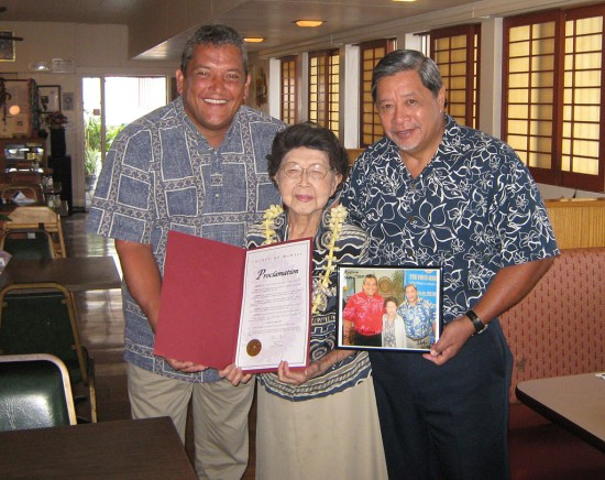 Mayor Billy Kenoi and Deputy Managing Director Wally Lau present Shizuko Teshima with a commendation recognizing her 102nd birthday in the landmark family restaurant, Teshima's, which is located in Honalo.