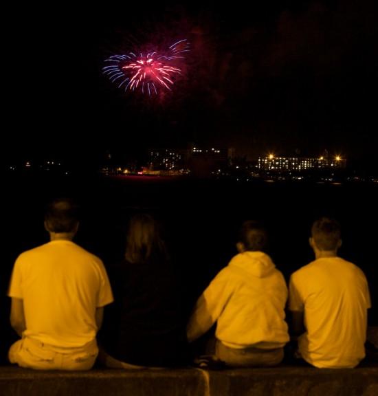 A fireworks burst creates a star over Hilo Bay.