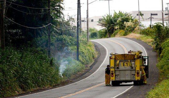 Fire/rescue crews await HELCO to arrive and shut-off power to an electrical line which went down on Waianuenue Avenue between Hospice of Hilo and Hilo Medical Center. The live power line started a grass fire alongside the road.
