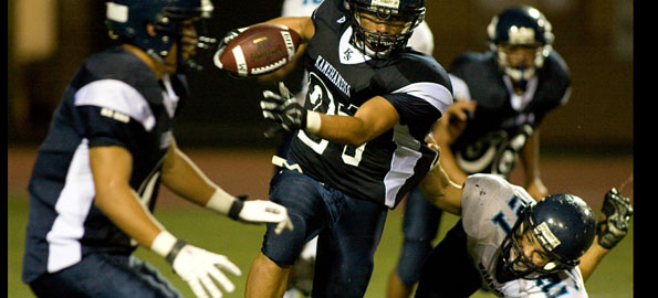 Kamehameha-Hawaii's Clyde Lewis (21) blasts his way through the Waiakea defense. Click on image above for video and photos from the game.