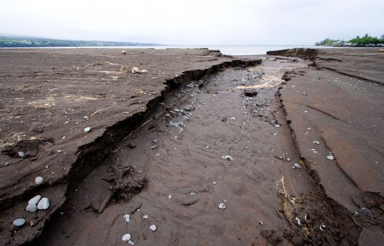 Heavy rains caused some erosion of the beach at Hilo Bay. The afternoon tide coming in worked to dull the jagged edge of the cut in the sand. Photography by Baron Sekiya for Hawaii 24/7.
