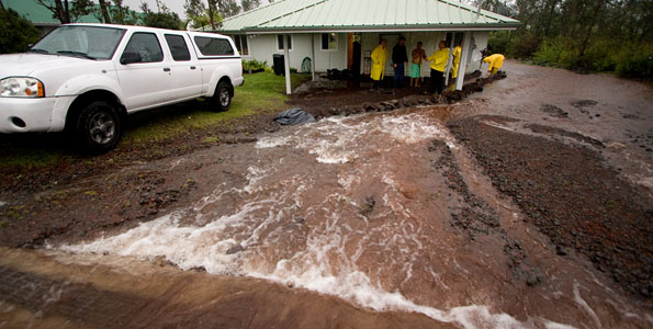 Firefighters protect a home from flood waters in Ainaloa Subdivision Saturday (Nov 14).