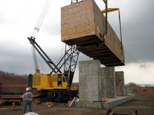 A crane positions the kiln over the support pylons.