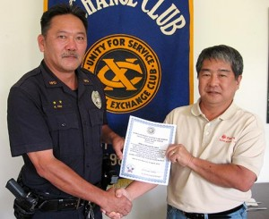 Aloha Exchange Club President Dale Tokuuke presents an 'Officer of the Month' award to Officer Kenneth Ishii