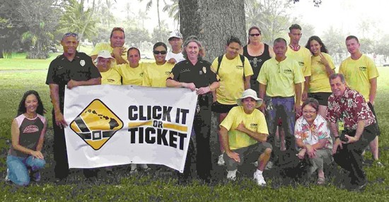 """Community Police Officer Todd Pataray and Sergeant Kelly Ka'aumoana-Matsumoto hold a """"Click It or Ticket"""" sign with community volunteers, who helped kick off this year's campaign with a sign-waving event Monday."""