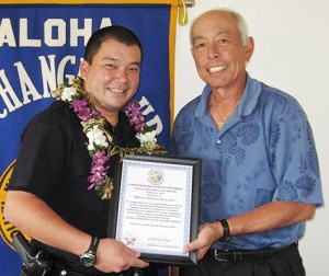 Aloha Exchange Club representative Joey Estrella presents an 'Officer of the Month' award to Officer Shawn Matsuda