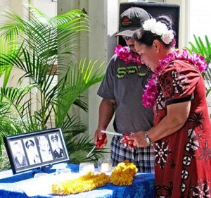 """Daniel Oili and Raynette Taketa, descendants of William """"Red"""" Oili, light candles in his honor and for three other Big Island police officers who have been killed in the line of duty since 1918."""