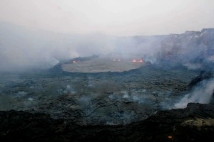 The lava pond in Pu`u `Ō `ō Crater has rebuilt its retaining walls and is once again perched 3-5 m (10-16 ft) above the surrounding crater floor. Photo courtesy of USGS/HVO