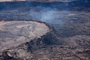 The lava lake'€™s levee stands up to 8 m (26 ft) above the surrounding crater floor. This steep-sided levee impounds the lava and forms what is called a '€œperched'€ lava lake. Pieces of the rim occasionally collapse into the lake, leading to sudden and fast-moving overflows of lava onto the crater floor. Photo courtesy of USGS/HVO