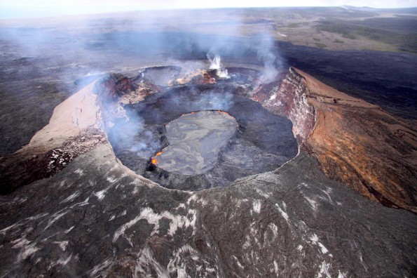 Aerial view looking southwest into Pu'u 'O'o crater with its lava lake (shiny surface) perched 5-8 m above the surrounding lava flows. The lake and flows have filled in the crater vertically at least 100 m (328 ft) since the crater collapsed on March 5, and still have about 12 m (39 ft) to reach the previous high point and begin spilling into the pits on the western crater rim (in background). The perched lava lake and high emissions of sulfur dioxide gas make the Pu'u 'O'o area extremely hazardous. Ground access is restricted by Hawai'i Volcanoes National Park and the Kahauale'a Natural Area Reserve managers.