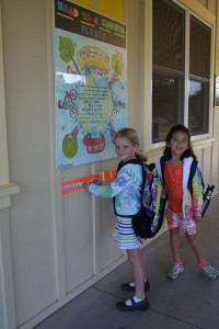 "After biking to school, 1st grader Sadie Blevins places the sticker she earned on the ""Road to a Greener Planet"" as classmate Nai'a Jones looks on."