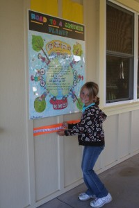 "3rd grader Jenna Blevins affixes on ""The Road to a Greener Planet,"" the sticker she earned for biking to school."