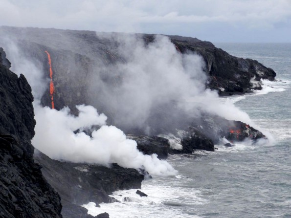 The current lava flow, coming down the pali and traversing the coastal plain, reached the ocean late last week. The ocean entry point is within the National Park, near its eastern border. Today, numerous small streams of lava were cascading over the sea cliff, and lava entering the water was starting to build a small delta. Photo courtesy of USGS/HVO