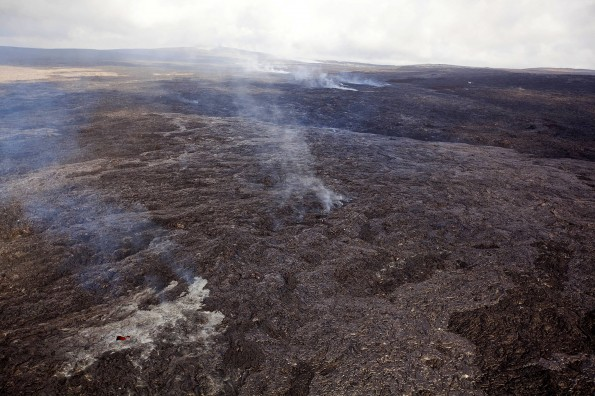 Higher up on the flow field, fume marks the trace of the lava tube. In the lower left portion of the photograph, a glowing skylight can be seen. Pu'u 'O'o is visible near the top of the photo. Photo courtesy of USGS/HVO