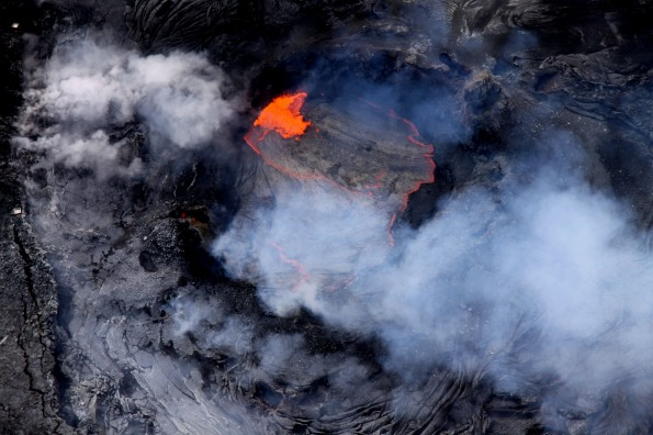 A lava pond has been active in a collapse pit in the eastern portion of Pu'u 'O'o crater for over a month now, with continuous roiling and spattering. For scale, two spatter collection trays - each slightly larger than a lunch tray - can be seen on the crater's rim at the left edge of the image. Photo courtesy of USGS/HVO