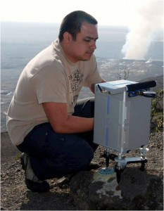 An HVO scientist measures gravity at a station on the rim of Kilauea caldera.  The plume from the summit eruption in Halema`uma`u Crater can be seen in the background. Photo courtesy of USGS/HVO