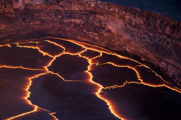 Incandescent lines mark the boundaries between migrating crustal plates on the surface of the lava lake in Halemaumau crater. Here, and at other lava lakes across the world, these rifting zones have a characteristic zigzag pattern. Photo courtesy of USGS/HVO