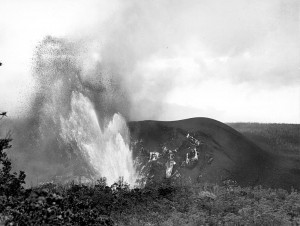 Hawaii Volcanoes National Park. 1959 eruption of Kilauea Volcano, third phase of activity in Kilauea Iki Crater. Reduced fountain deflected northward by the collapse of the inner part of the cone in the crater. Note the new cone developing on the left shoulder of the old main cone (immediately to the right of the fountain). View is from the trail leading down to Byron Ledge. 8:00 a.m., November 29, 1959. Photo courtesy of USGS