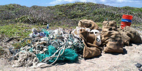 """The 209.6 lbs of """"marine debris"""" loot (e.g., fishing nets, miscellaneous plastic debris and a bucketful of microplastics) during less than an hour of scouring by HWF and volunteers at Kamilo. (Photo courtesy of Harold Leatherman 