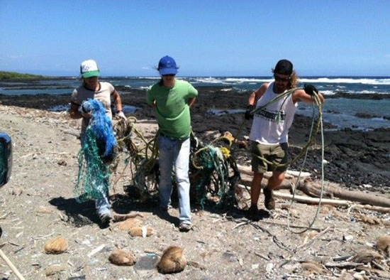 HWF's Megan Lamson, Stacey Breining and Patrick Leatherman pulling up a large derelict fishing net from the rocky nearshore of Kamilo before CNN interview. (Photo courtesy of Harold Leatherman | HWF volunteer)